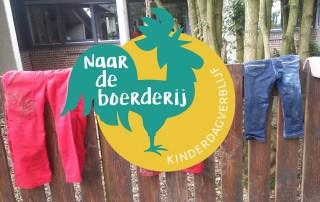 Houten hekje met overalls voor kinderen op het terrein van kinderdagverblijf Naar de boerderij.